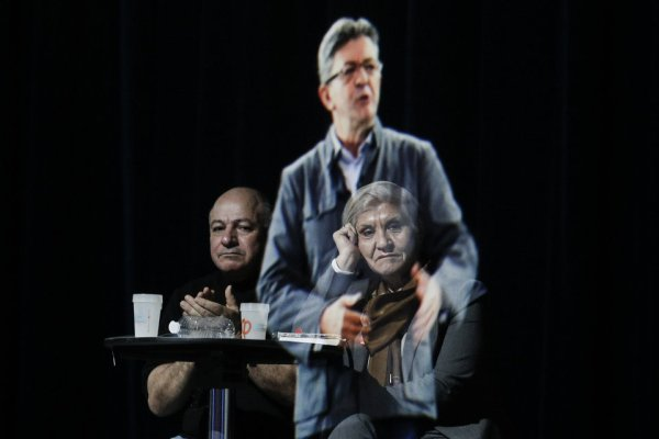 People sit at a table on stage and look towards the hologram of hard-left French presidential candidate Jean-Luc Melenchon, as he speaks to supporters who are gathered in Saint-Denis, near Paris, Sunday, Feb. 5, 2017. As Melenchon holds a rally in Lyon Sunday, a hologram of him is being projected by satellite to crowds in Paris. (AP Photo/Kamil Zihnioglu)