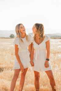 happy trendy girlfriends having fun in countryside field
