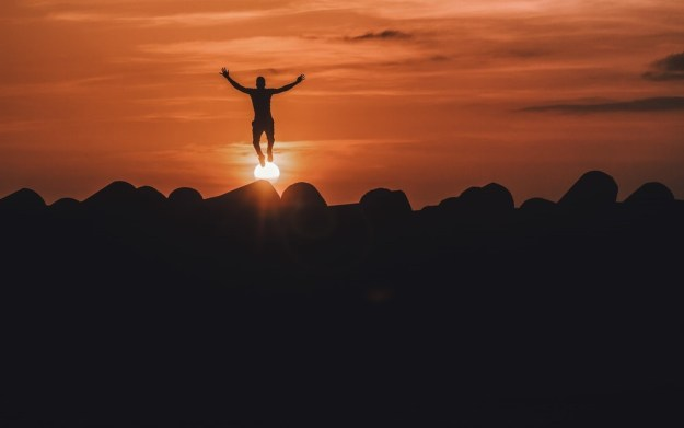silhouette of person jumping in mid air