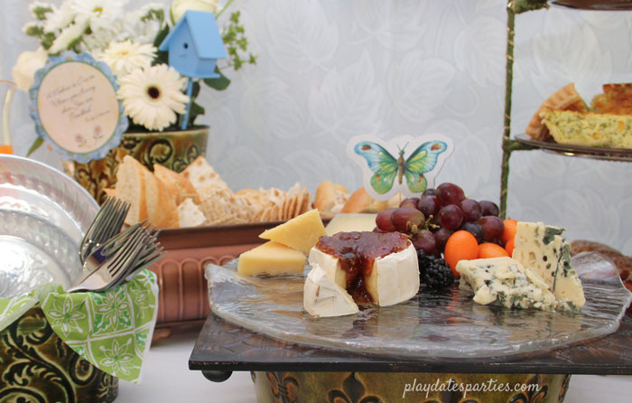 A pretty cheese board for a Mother's Day brunch with blue and green accents