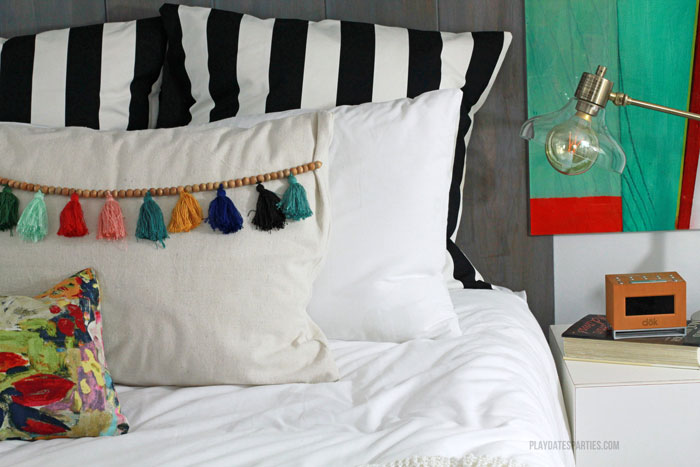 With a neutral textured palette, this modern boho master bedroom shows that you don't need to have a huge bedroom to have function and beauty. Don't forget to check out the customized Ikea storage wall, tassel trim pillows, and bold black striped accents.