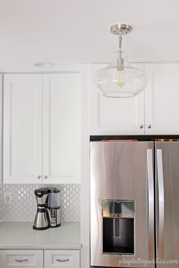 Small white kitchen, big on style. Faux marble #quartz countertops, beveled #white #tile backsplash, and a clear glass urn pendant add charm to this neutral home #design.