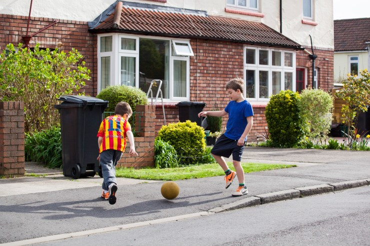 Two boys play out on pavement