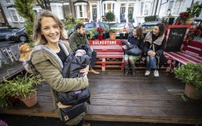 A Parklet in Hackney, London, with a young woman holding a baby standing and smiling at the camera, and 3 people sitting behind her on benches
