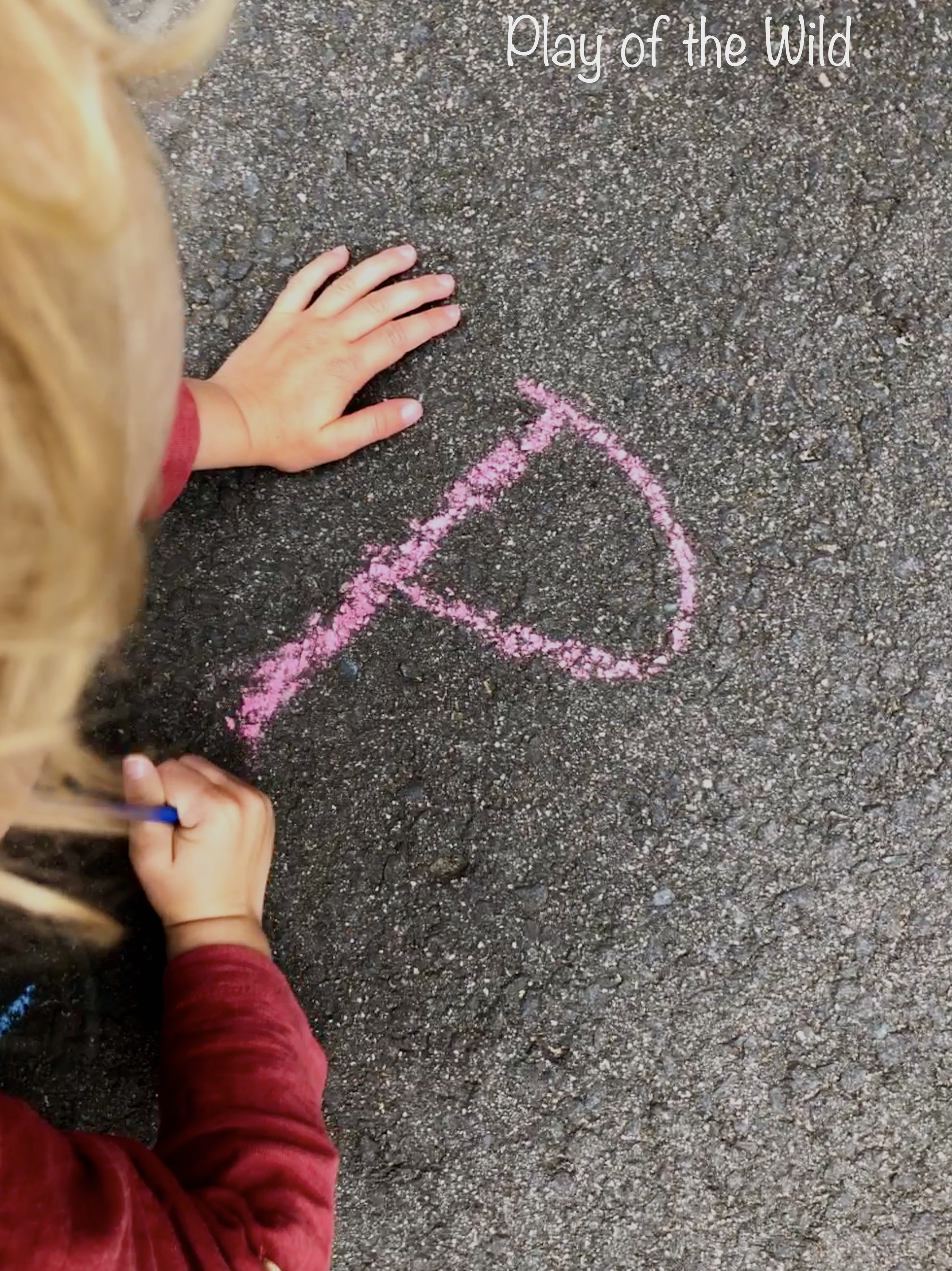 Painting chalk letters with water for EYFS.