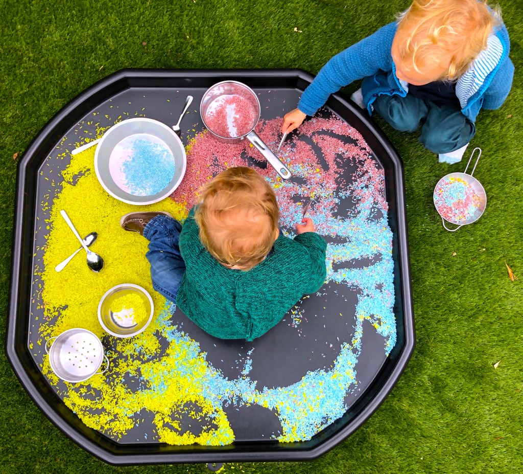 Loose parts play ideas for toddlers. pouring and mixing colourful rice.