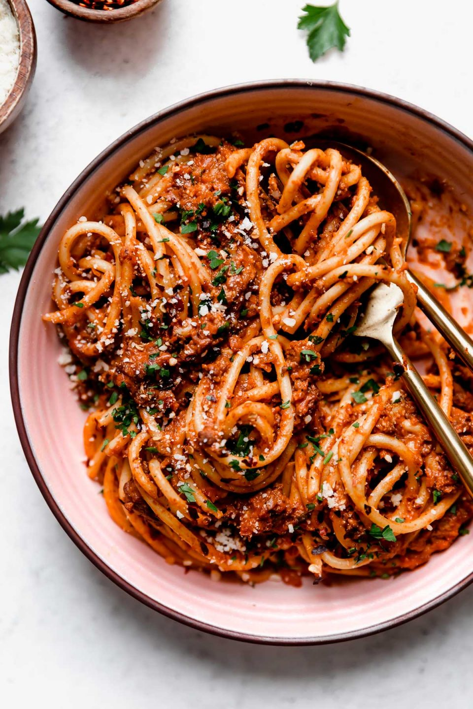 Bolognese sauce tossed into bucatini noodles, served in a pink pasta bowl with gold flatware. The pasta bolognese is topped with grated cheese, chopped parsley, & crushed red pepper flakes.