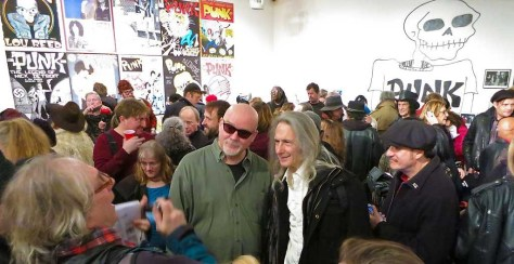 John Holmstrom and Lenny Kaye pose for a photo while Monte Melnick looks on, at the opening of the Punk Magazine 40th Anniversary Exhibition at Howl Happening gallery in NYC.