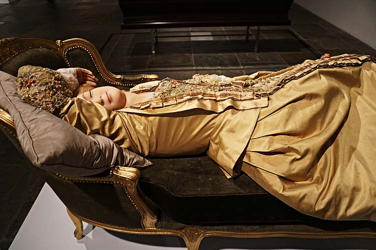 "Phillippe Curtis, Swiss, 1737-1794 ""Sleeping Beauty, 1989, after 1765 original: gold leaf, wood, velvet upholstery, beeswax, human hair, fiberglass, alloy and steel servo, slush wax, silk and lace."" ""Lifelike images of swooning and cataleptic women known as Sleeping Beauties became popular forms of fairground entertainment in the eighteenth century. Male onlookers took pleasure in viewing these passive female bodies and determining whether they were real or robotic. The Swiss wax modeler Curtisus based this automaton on a figure of public titillation, Louis XV's famous mistress Madame du Barry."""