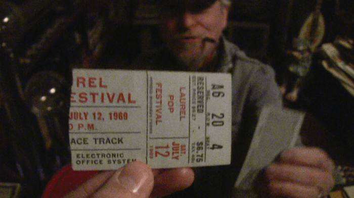 Tom Beach holding one of two tickets he has to the Laurel Pop Festival, a two day pop festival one month before Woodstock at the Laurel Racecourse in Laurel, Maryland. Led Zeppelin headlined one of the nights. Tom was there both nights. He also went to Woodstock.