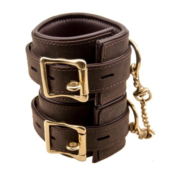 A pair off Bound Nubuck Leather wristcuffs with large brass buckles and linking chain stacked on top of each other