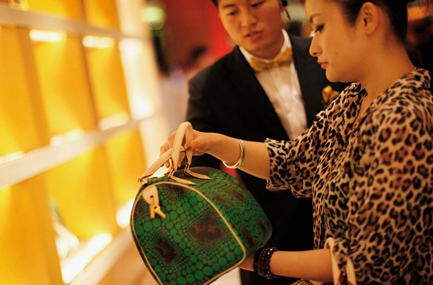 mujer comprando bolsa cara