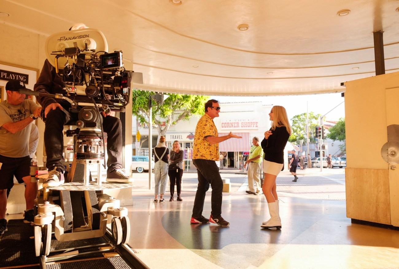 El director Quentin Tarantino y Margot Robbie como Sharon Tate conversando en el set de Once Upon a Time in Hollywood (2019). Imagen: Andrew Cooper/Columbia