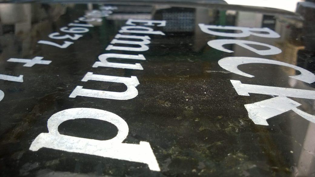 litery grawerowane na tablicy granitowej