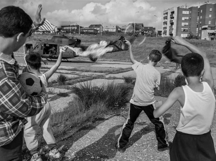 Fëmijët shqiptarë përshëndesin helikopterin e Natos që zbarkon pranë palestrës 1 Tetori në Prishtinë (Jukka Male, 1999)