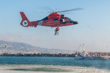 HH-65 Dolphin, USCG Helicopter, lifts rescue diver from water.