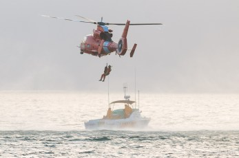 HH-65 Dolphin, USCG Helicopter, lifts rescue victim from Lifeguard boat.