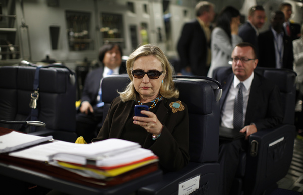 U.S. Secretary of State Hillary Clinton checks her PDA upon departure in a military C-17 plane from Malta bound for Tripoli, Libya October 18, 2011. REUTERS/Kevin Lamarque (UNITED STATES) POOL
