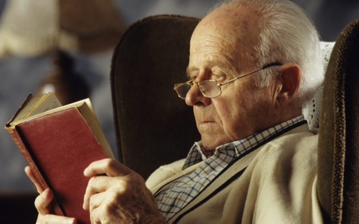 Senior man wearing spectacles reading book in living room, close-up