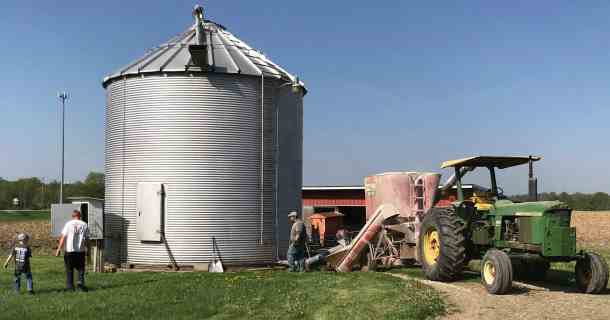 feed grinder filling up with corn at grain bin on a farm