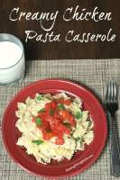 Crock Pot chicken pasta casserole on a red plate by a glass of milk