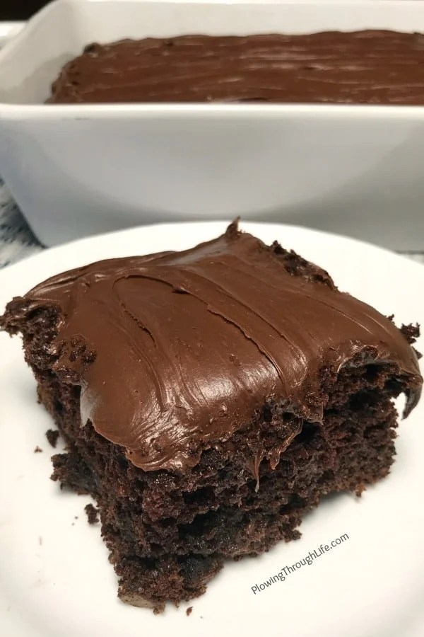 piece of super moist chocolate cake with chocolate icing on a white plate in front of 9x13 pan of cake