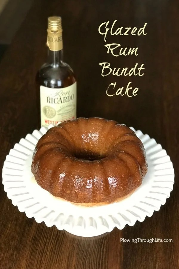 Bottle of rum next to rum glazed bundt cake on a white cake stand