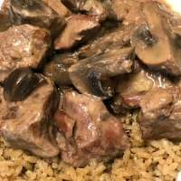 close-up beef stew meat and mushrooms on rice