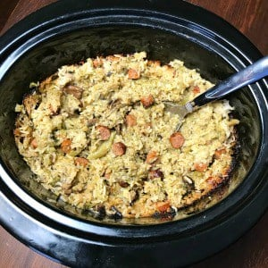 Sausage Link, Broccoli and Rice casserole in a Crock Pot with a serving spoon