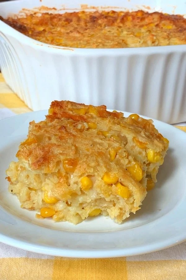square piece of corn casserole on a plate by casserole dish made with Swiss cheese, eggs, crackers and more