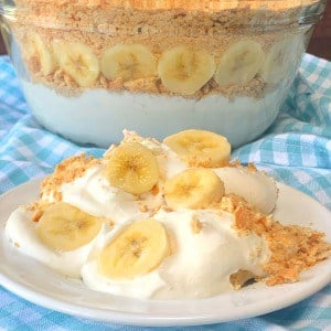 Banana cream and graham cracker dessert on a plate next to a bowl of banana creamer