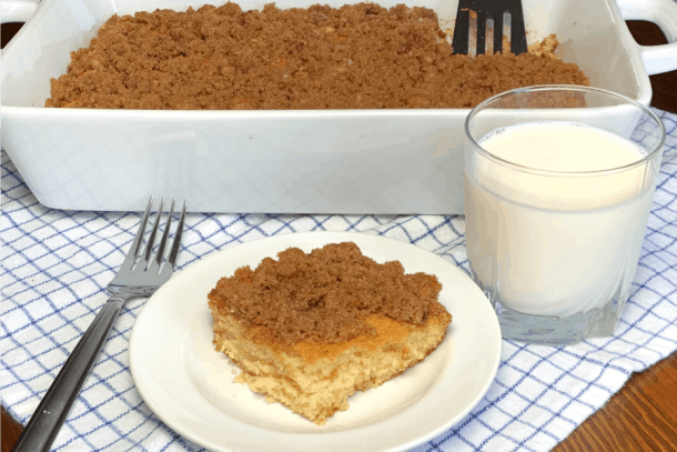 9x13 pan of Amish buttermilk coffee cake with a piece on a plate and glass of milk