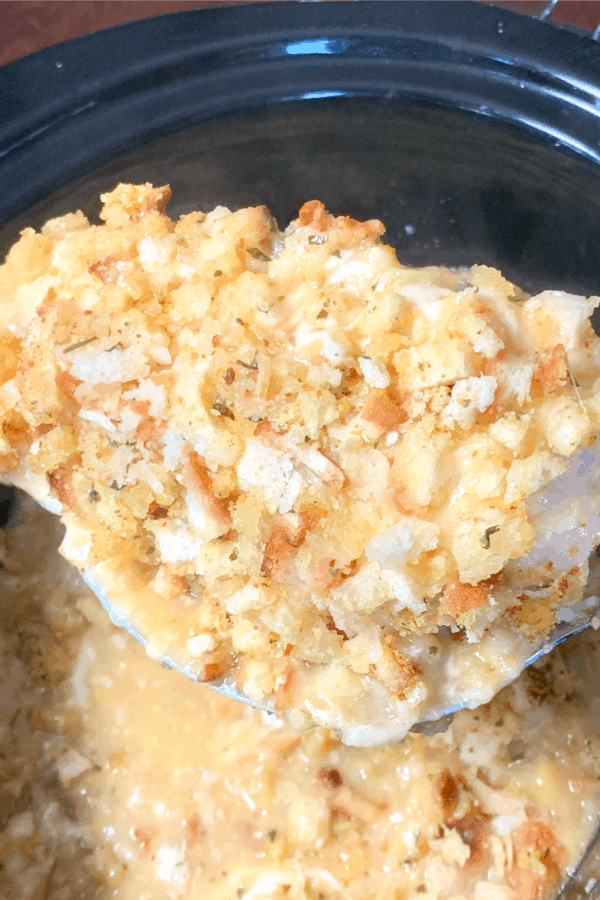 Spoon of chicken covered in stuffing over crock pot