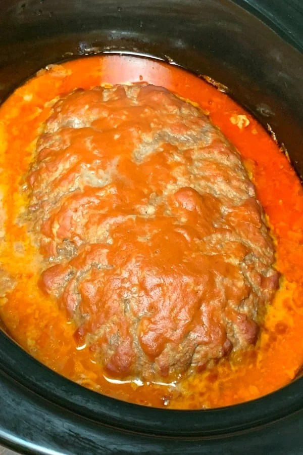 rectangular applesauce meatloaf in crock pot covered by tomato soup