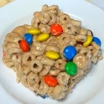 Square Cheerio cereal bar with M&Ms on a white plate