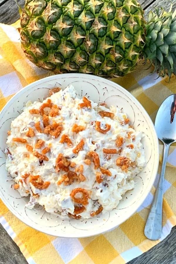 Bowl of no-bake pineapple pretzel salad next to whole pineapple