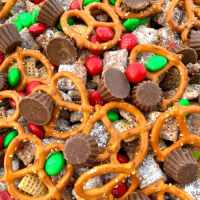 Powdered sugar covered chex cereal, mini reeses cups, M&Ms and pretzels make Christmas Puppy Chow