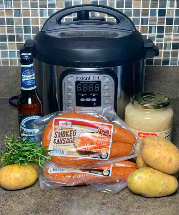 ingredients needed to make Instant pot sausage and sauerkraut on the counter - instant pot, smoked sausage, sauerkraut, potatoes, beer and rosemary