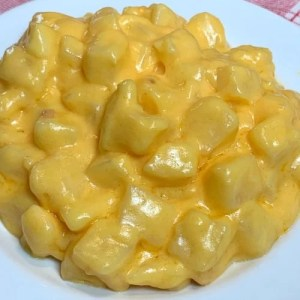 Scoop of cheesy potatoes on a white plate