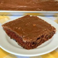 Chocolate Texas brownie on a small white plate on a yellow plaid napkin
