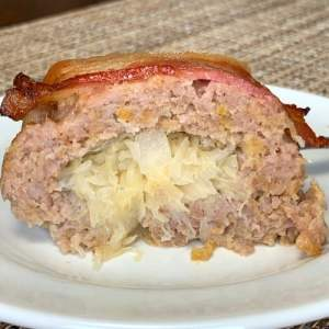 Slice of ground pork and sauerkraut roll topped with a slice of bacon