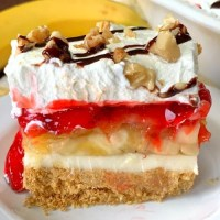 Piece of strawberry banana split cake with fresh banana in background