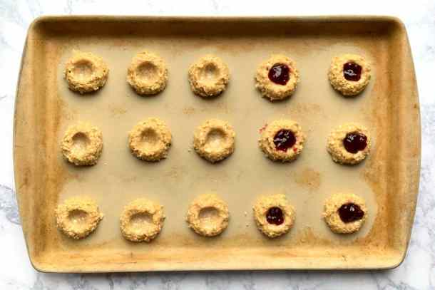 Cookie dough on baking sheet with thumbprint for jam