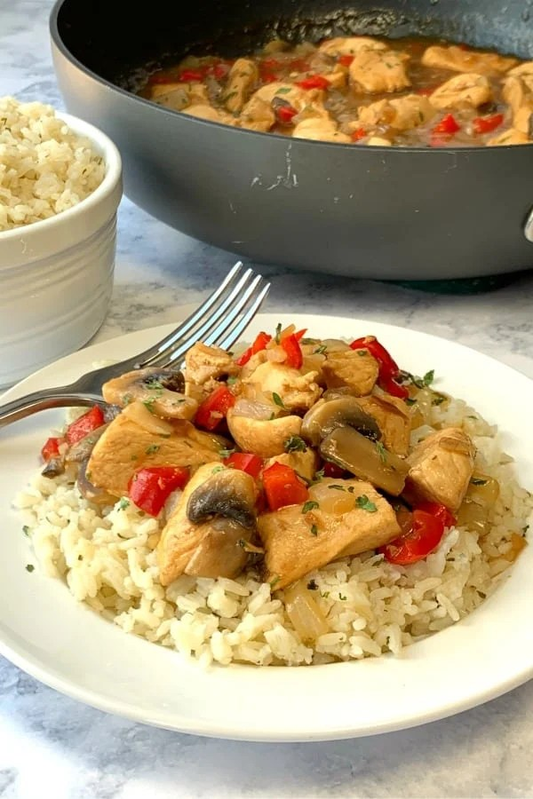 Saucy chicken over rice on marble countertop by skillet and rice bowl