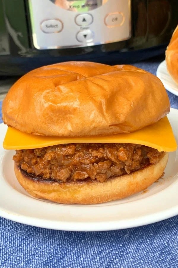 Sloppy Joe sandwich with cheese on white plate in front of a crock pot