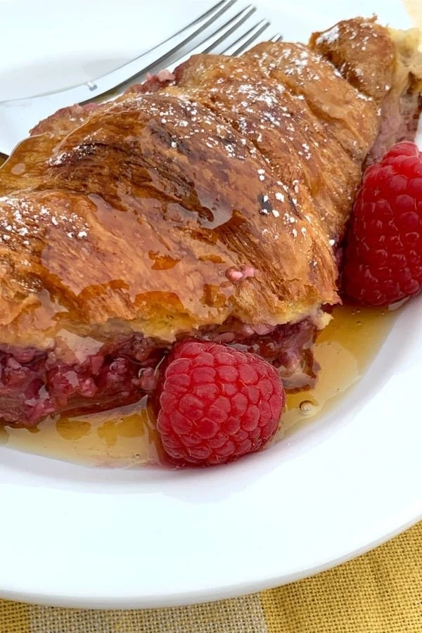 Close up raspberry and cream cheese stuffed croissant French toast with maple syrup