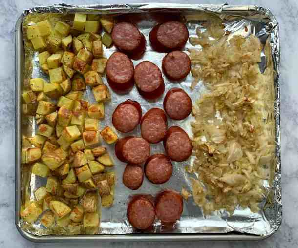 Cubed potatoes, smoked sausage and sauerkraut on air fryer tray