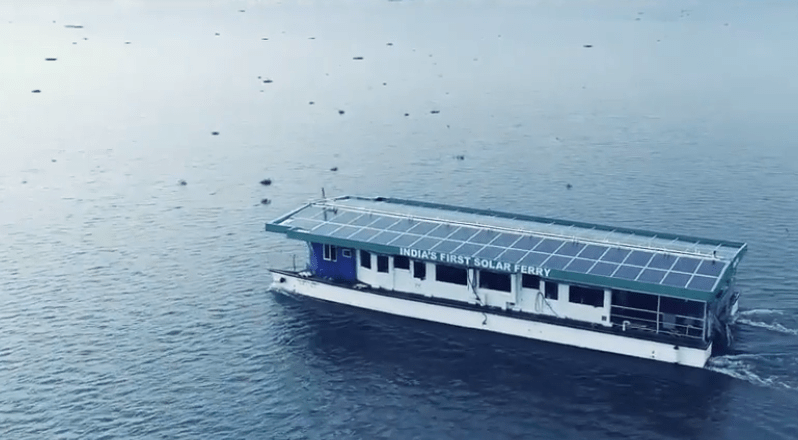 A fery boat with solar panels on top crossing a river