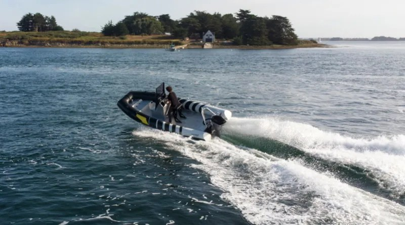 An rigid hull inflatable boat with a wake behind it races by an island