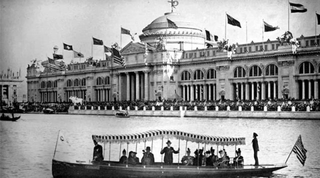 long electric boats with fringed roofs on the lake in front of a large building at the 1893 Chicago World's Fair